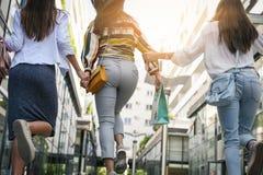 Trois jeunes femmes à la mode flânant avec des paniers de Images libres de droits