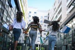 Trois jeunes femmes à la mode flânant avec des paniers de Images stock