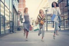 Trois jeunes femmes à la mode flânant avec des paniers Sati Photographie stock