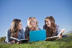 Trois jeunes femmes étudiant dans l'extérieur photos stock