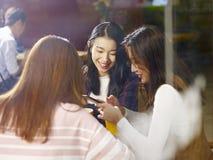Trois jeunes femmes asiatiques causant parler dans le café Image stock