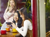 Trois jeunes femmes asiatiques regardant le téléphone portable et riant dedans Photographie stock libre de droits