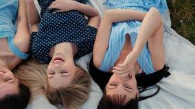 Trois jeunes femmes attirantes se trouvent sur un plaid et regardent le ciel Rire et point, danse Amies de repos clips vidéos
