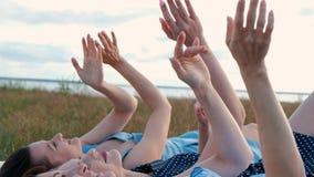 Trois jeunes femmes attirantes se trouvent sur un plaid et regardent le ciel Rire et point, danse Amies de repos banque de vidéos