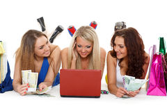 Trois jeunes femmes avec l'ordinateur portable. Achat. Photo stock