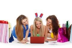 Trois jeunes femmes avec l'ordinateur portable. Achat. Image libre de droits