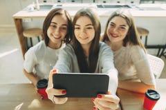 Trois jeunes femmes ayant l'amusement et prenant le selfie Photos libres de droits