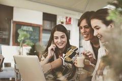 Trois jeunes femmes ayant la conversation en café Images libres de droits