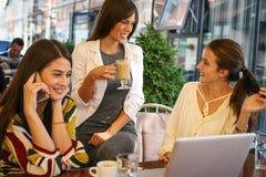 Trois jeunes femmes ayant la conversation en café et à l'aide de l'ordinateur portable Image libre de droits