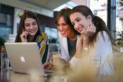 Trois jeunes femmes ayant la conversation en café et à l'aide de l'ordinateur portable Images libres de droits