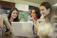 Trois jeunes femmes ayant la conversation en café et à l'aide de l'ordinateur portable Photographie stock