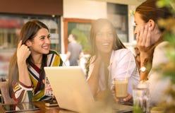 Trois jeunes femmes ayant la conversation en café et à l'aide de l'ordinateur portable Image stock