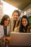 Trois jeunes femmes ayant la conversation en café et à l'aide de l'ordinateur portable Images stock
