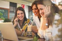 Trois jeunes femmes ayant la conversation en café et à l'aide de l'ordinateur portable Photographie stock libre de droits