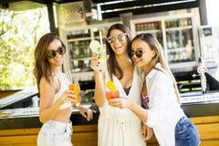 Trois jeunes femmes buvant des coctais dans la barre de plage Image stock