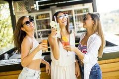 Trois jeunes femmes buvant des coctais dans la barre de plage Photo stock