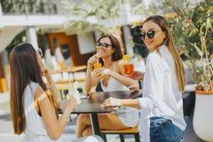 Trois jeunes femmes buvant des coctais dans la barre de plage Images stock