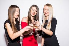 Trois jeunes femmes célébrant et buvant du champagne sur la partie Photo stock
