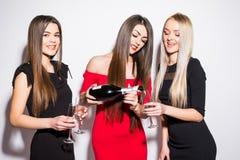 Trois jeunes femmes célébrant et buvant du champagne sur la partie Photo libre de droits