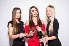 Trois jeunes femmes célébrant et buvant du champagne sur la partie Photos libres de droits