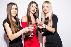 Trois jeunes femmes célébrant et buvant du champagne sur la partie Photographie stock libre de droits