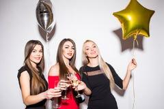 Trois jeunes femmes célébrant et buvant du champagne sur la partie Image libre de droits