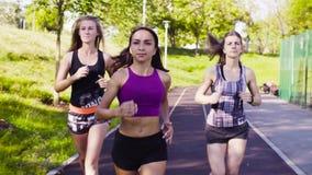 Trois jeunes femmes courant à l'au sol de sports banque de vidéos