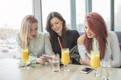 Trois jeunes femmes d'attractie à l'aide du téléphone portable au café Image libre de droits