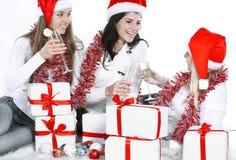 trois jeunes femmes dans des chapeaux de Santa Claus avec des cadeaux de Noël et des verres de champagne Photo stock