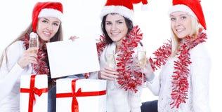 trois jeunes femmes dans des chapeaux de Santa Claus avec des cadeaux de Noël pour notre Noël Photo libre de droits