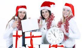 Trois jeunes femmes dans des chapeaux de Santa Claus avec les cadeaux f de Noël Photo stock