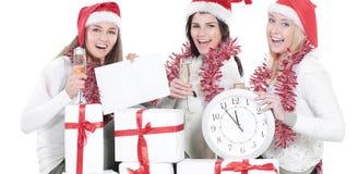 Trois jeunes femmes dans des chapeaux de Santa Claus avec les cadeaux f de Noël Photos libres de droits