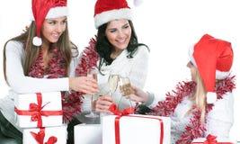Trois jeunes femmes dans des chapeaux de Santa Claus avec les cadeaux a de Noël Photos libres de droits