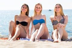 Trois jeunes femmes dans le bikini sur la plage sablonneuse Photographie stock