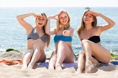 Trois jeunes femmes dans le bikini sur la plage sablonneuse Images stock