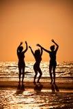Trois jeunes femmes dansant sur la plage au coucher du soleil Photos stock