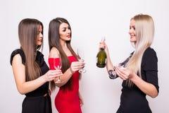 Trois jeunes femmes de sourire célébrant et buvant du champagne sur la partie Images libres de droits