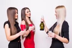 Trois jeunes femmes de sourire célébrant et buvant du champagne sur la partie Image stock