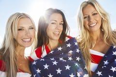 Trois jeunes femmes enveloppées dans les drapeaux américains sur une plage Image libre de droits