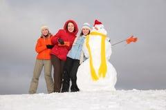 Trois jeunes femmes et bonhomme de neige 3 Images stock