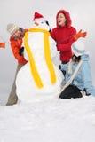 Trois jeunes femmes et bonhomme de neige Photographie stock