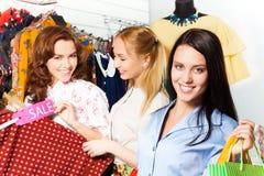 Trois jeunes femmes faisant des emplettes ensemble dans la boutique Images libres de droits
