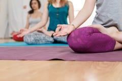 Trois jeunes femmes faisant le yoga et méditant en position de Lotus Photo libre de droits