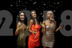 Trois jeunes femmes gaies ayant la partie et buvant du champagne au-dessus du fond foncé Image stock