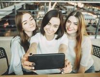 Trois jeunes femmes heureuses prenant le selfie au café Photo libre de droits