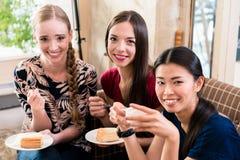 Trois jeunes femmes mangeant le gâteau à l'intérieur Images libres de droits