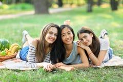 Trois jeunes femmes multiraciales heureuses se trouvant sur l'herbe en parc Photographie stock