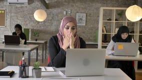 Trois jeunes femmes musulmanes dans le hijab se reposant et fonctionnant dans le bureau moderne, beau baîllement musulman de femm clips vidéos