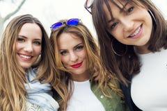 Trois jeunes femmes parlant et riant dans la rue Images stock