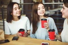 Trois jeunes femmes parlant et riant du café Image stock